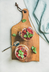 Healthy breakfast glasses on wooden board  top view