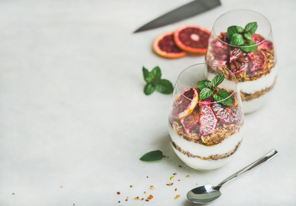 Greek yogurt granola and blood orange layered parfait in glasses