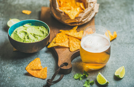 Mexican corn chips  fresh lime  guacamole sauce and wheat beer