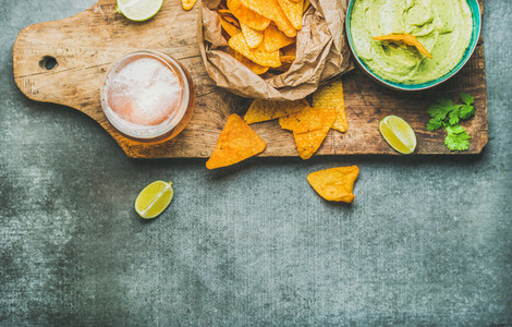 Guacamole sauce  corn chips  beer in glass  copy space