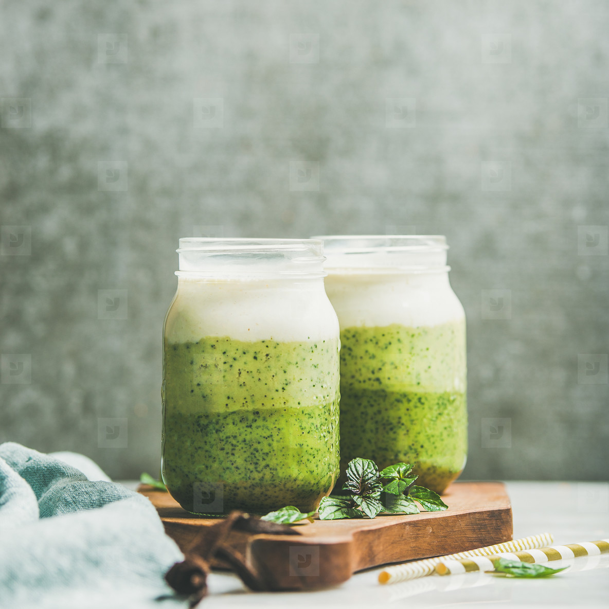 Ombre layered green smoothies with mint leaves in glass jars