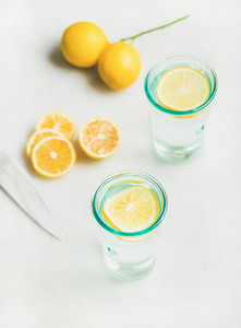 Detox lemon water in glasses served with fresh lemon fruits