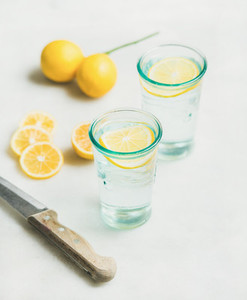 Morning detox lemon water in glasses and fresh lemons