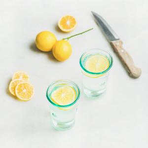 Morning detox lemon water in glasses over grey marble background