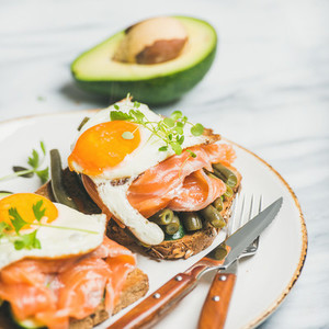 Salmon  avocado  fried egg  beans and sprouts sandwiches  square crop