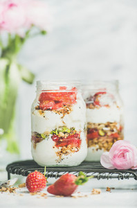 Greek yogurt  granola  fresh strawberry breakfast jars  pink raninkulus flowers