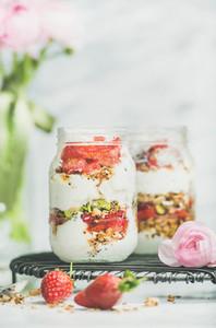 Greek yogurt  granola  fresh strawberry breakfast jars  pink raninkulus flowers
