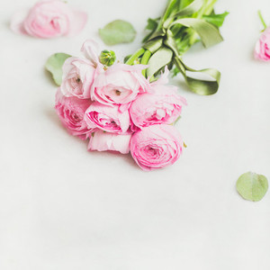 Light pink spring ranunkulus flowers on white marble background
