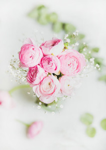 Light pink ranunkulus flowers on marble background  top view