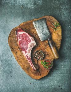 Dry aged raw beef rib eye steak on board