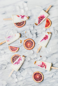 Blood orange  yogurt and granola popsicles on ice cubes