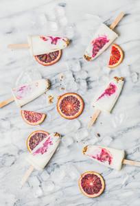 Blood orange yogurt and granola popsicles on ice cubes
