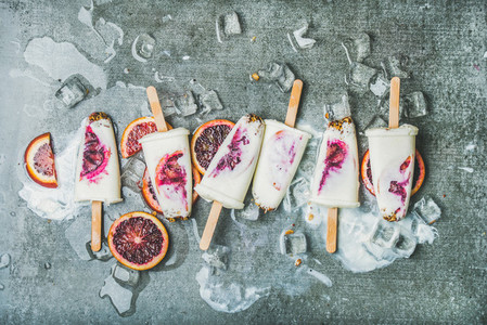 Red orange yogurt granola popsicles on ice cubes grey background