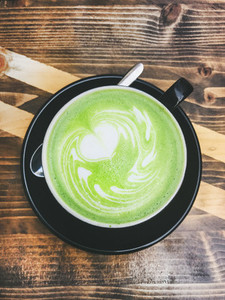 Cup of matcha latte in black cup on wooden background