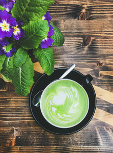Cup of matcha latte and bright flowers on wooden table
