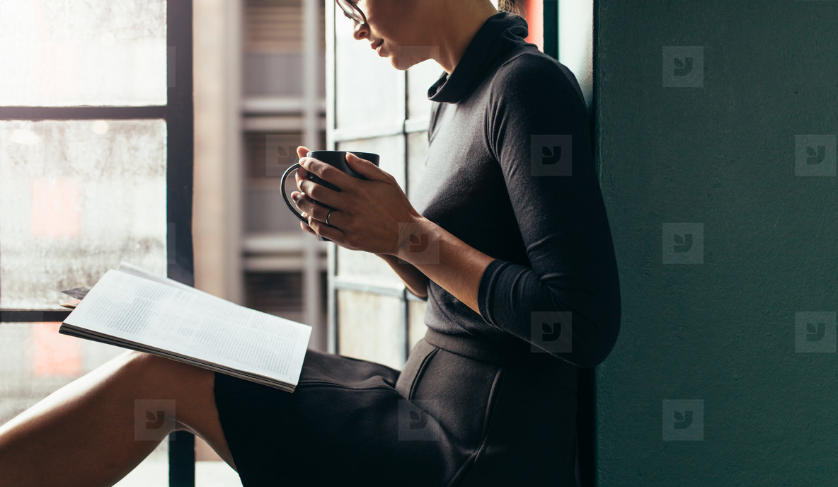 Woman reading magazine with coffee