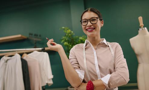 Attractive fashion designer standing in her creative studio