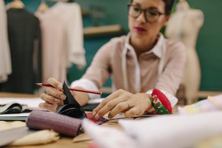Female dressmaker choosing fabric from swatch