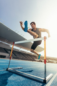 Athlete jumping over an hurdle on running track