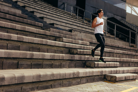 Athlete running down the stairs of a stadium stand