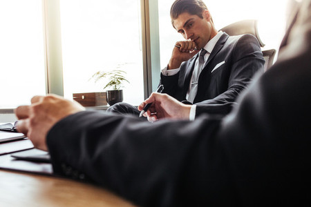 Thoughtful businessman sitting at his desk with partner