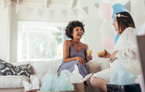 Happy pregnant woman and her friend at baby shower