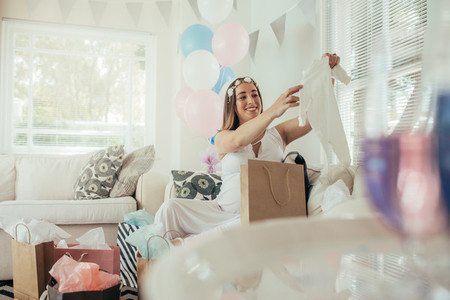Pregnant woman opening a new gift after baby shower