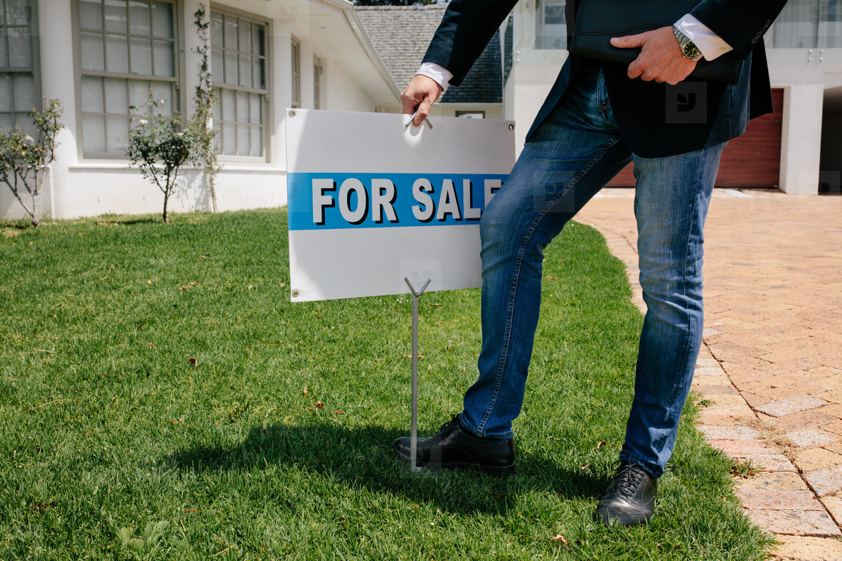 Realtor with a for sale sign board outside a house