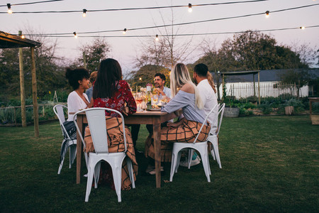 Group of friends having dinner in garden restaurant