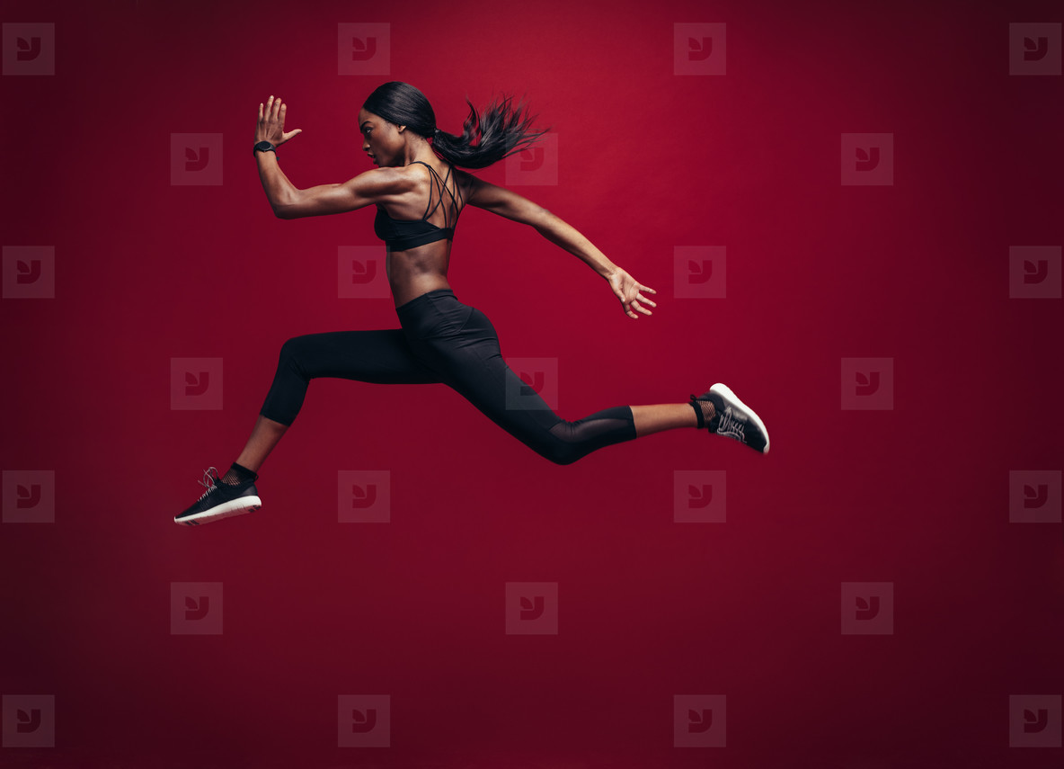 Female athlete running and jumping