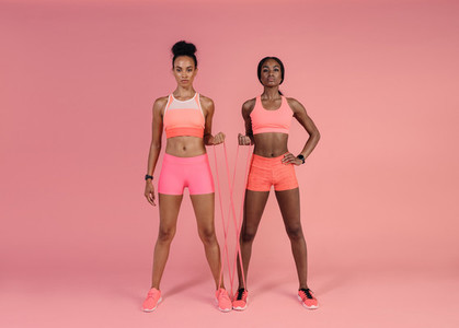 Two women doing exercises with resistance band