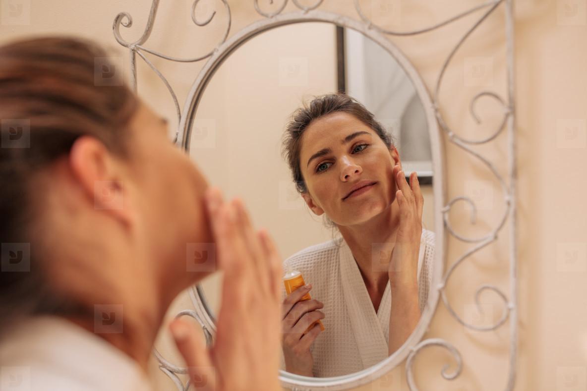 Female in mirror applying cream on her face