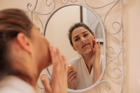 Female in mirror applying cream on her face