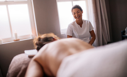 Masseur talking with female lying on massage table in spa salon