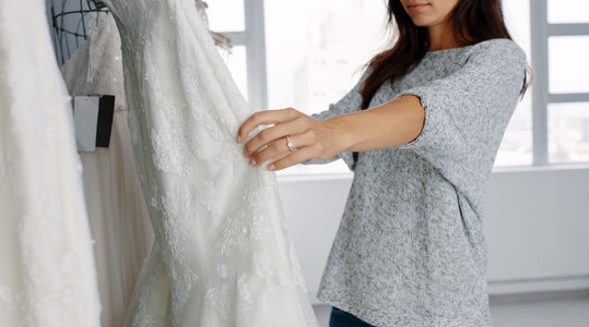 Woman looking at bridal gowns on display in boutique