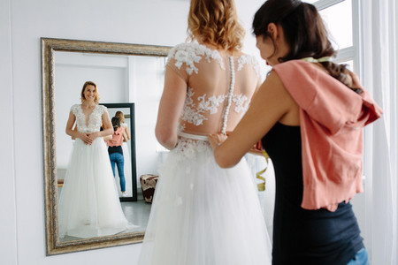 Bride trying on wedding dress in a shop