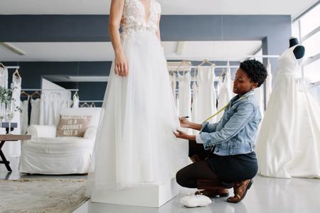 Woman making adjustment to wedding gown in designer studio