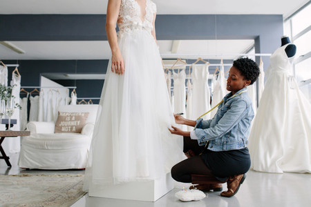 Woman making adjustment to wedding gown in designer studio