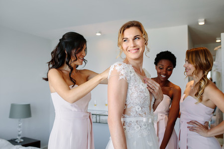 Friends dressing the bride for wedding