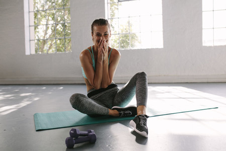 Smiling female resting after training at gym