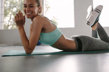 Smiling female resting after fitness training