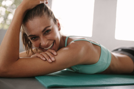 Fit female lying on exercise mat in gym and smiling