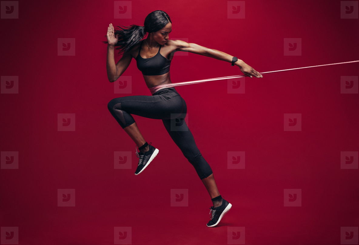 Sporty woman exercising with resistance band