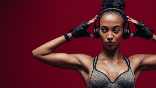 Muscular african female exercising with headphones on
