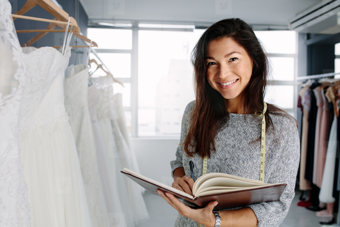 Beautiful female bridal store owner with a diary