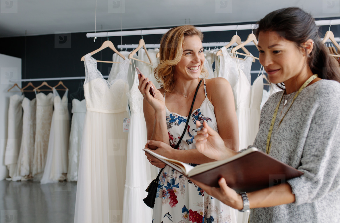 Bridal store owner taking order from client