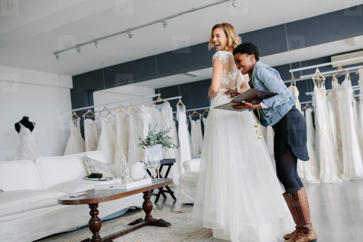 Female Trying On Wedding Gown With Women Assistant In Shop