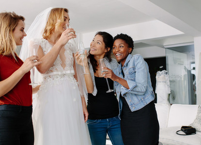 Bride drinking champagne with friends in bridal boutique