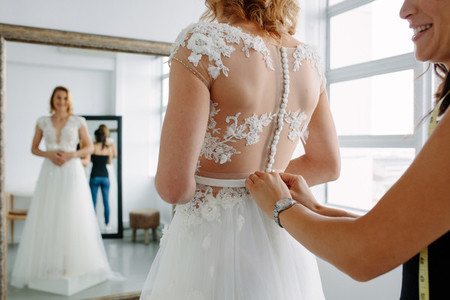 Making final touch on tailor made gown in bridal shop