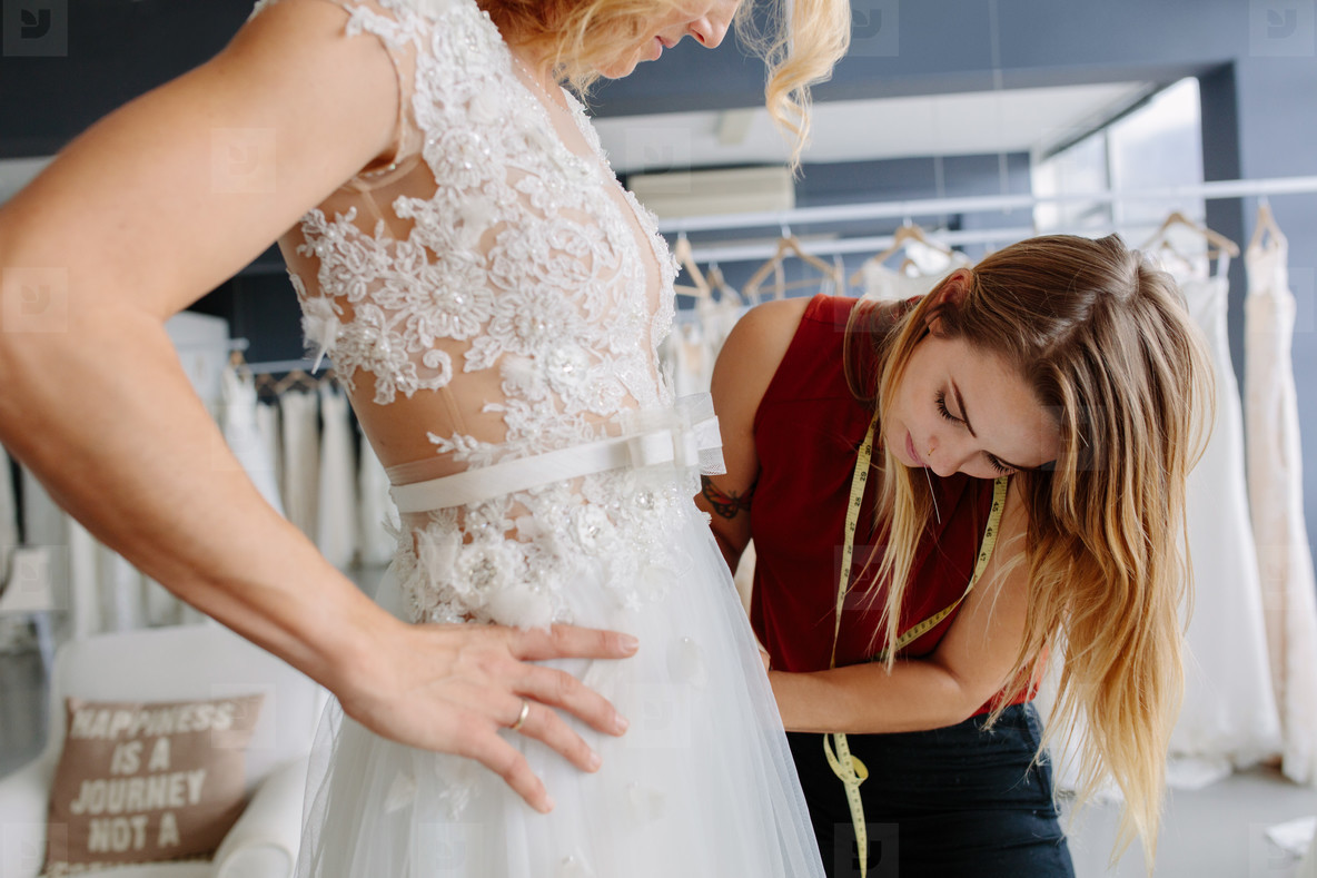 Skillful designer fitting bridal gown to bride
